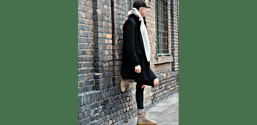 Изображение мужской белой толстовки с черным пальто и зауженными джинсами